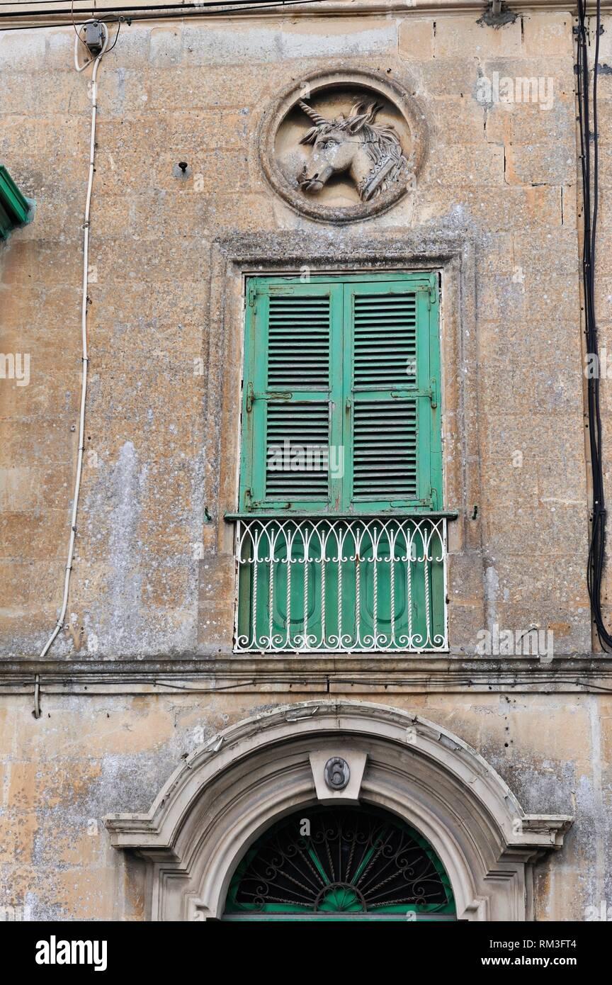 facade with a sculpted unicorn in medallion, Mdina, Malta, Mediterranean Sea, Southern Europe. - Stock Image