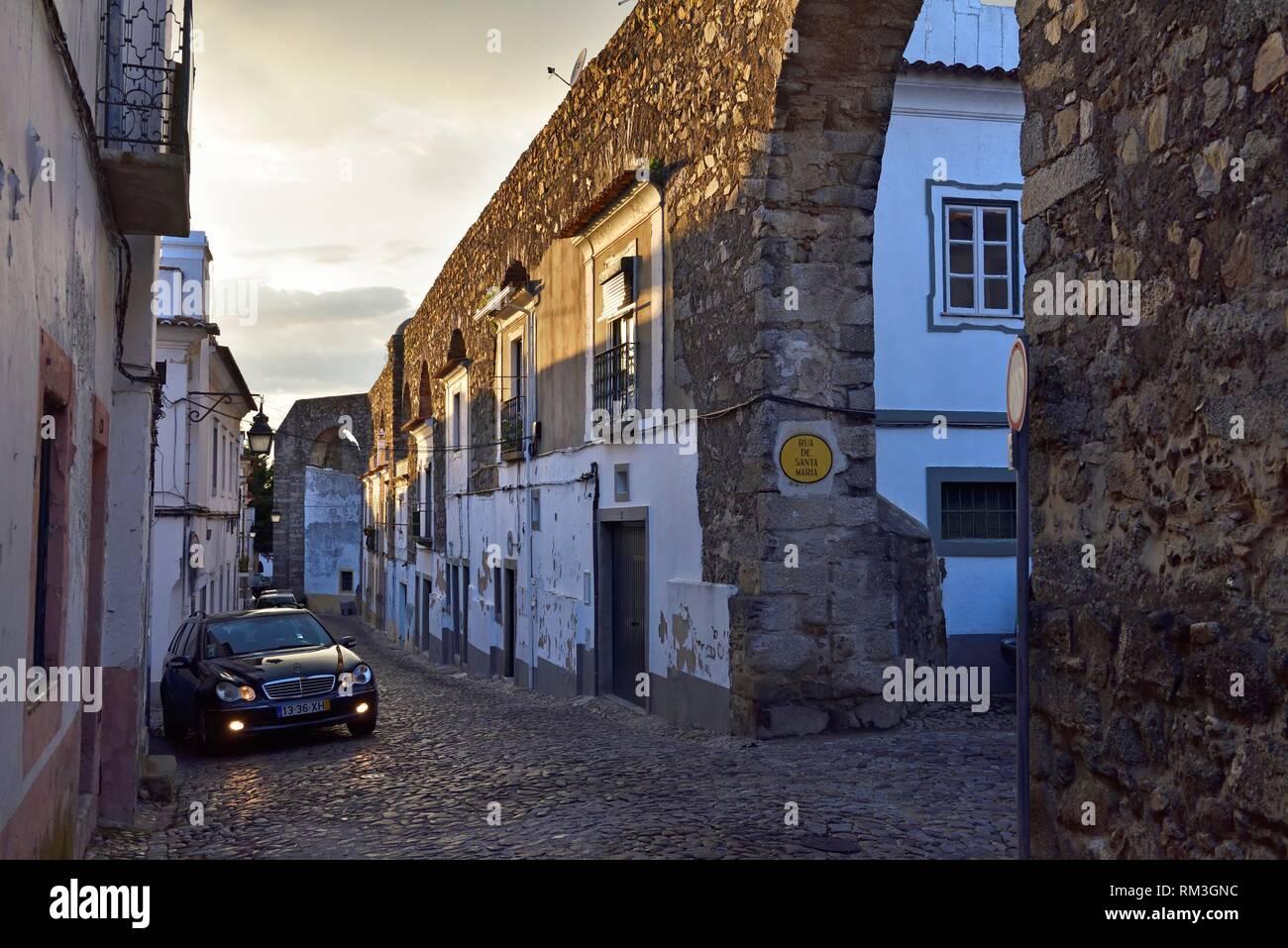 houses built between the arches of the Prata Aqueduct, Rua do Cano, Evora, Alentejo region, Portugal, southwertern Europe. - Stock Image