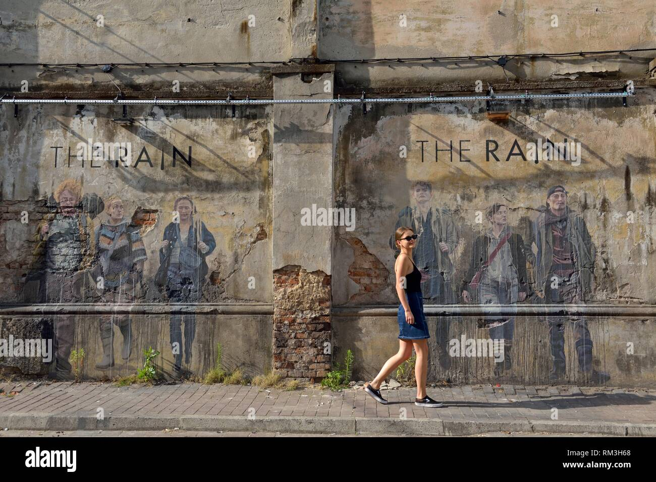 young woman walking in front a wall, with a graffiti from the Danish TV series ´´The Rain´´, within Tytano, Urban Lifestyle Complex installed in a - Stock Image