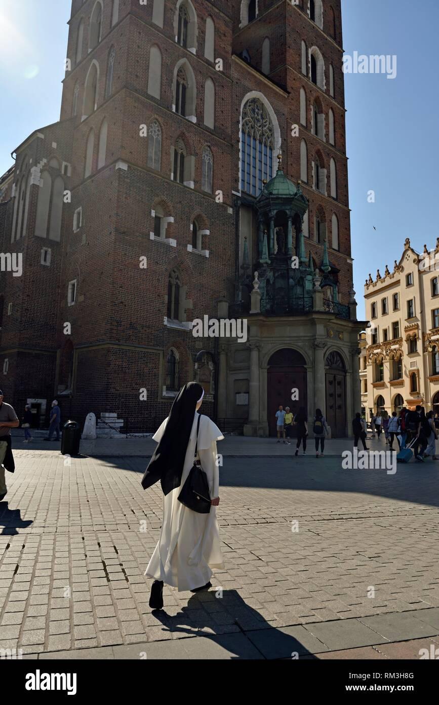 catholic nun walking beside Saint Mary´s Basilica, Rynek Glowny, the main square of the Old Town of Krakow, Malopolska Province (Lesser Poland), - Stock Image