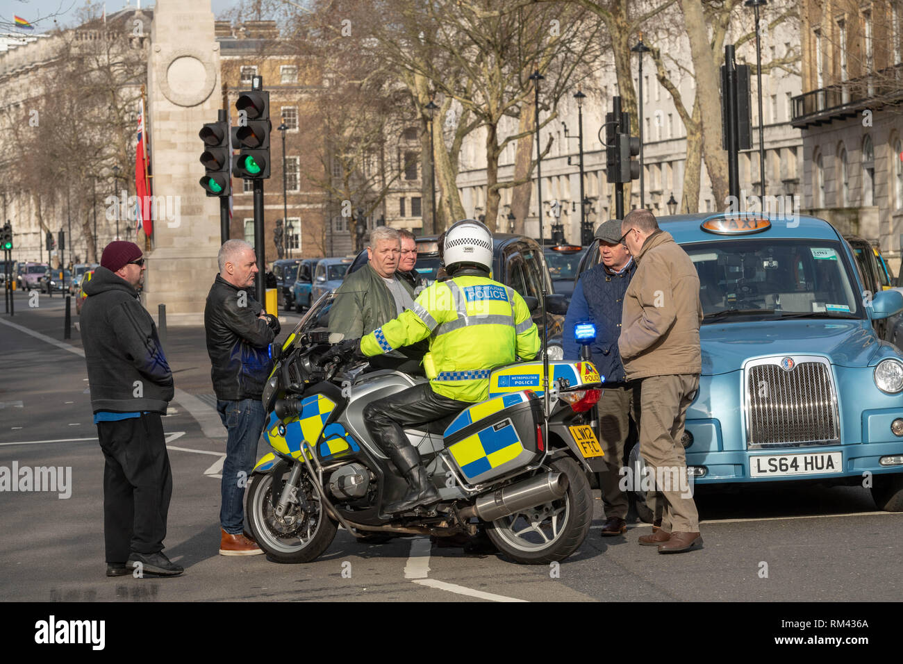 London, UK. 13th February 2019, London, UK. taxi protest closes roads around Parliament A police officer speaks to cab drivers to get them to move along Credit Ian Davidson/Alamy Live News Stock Photo