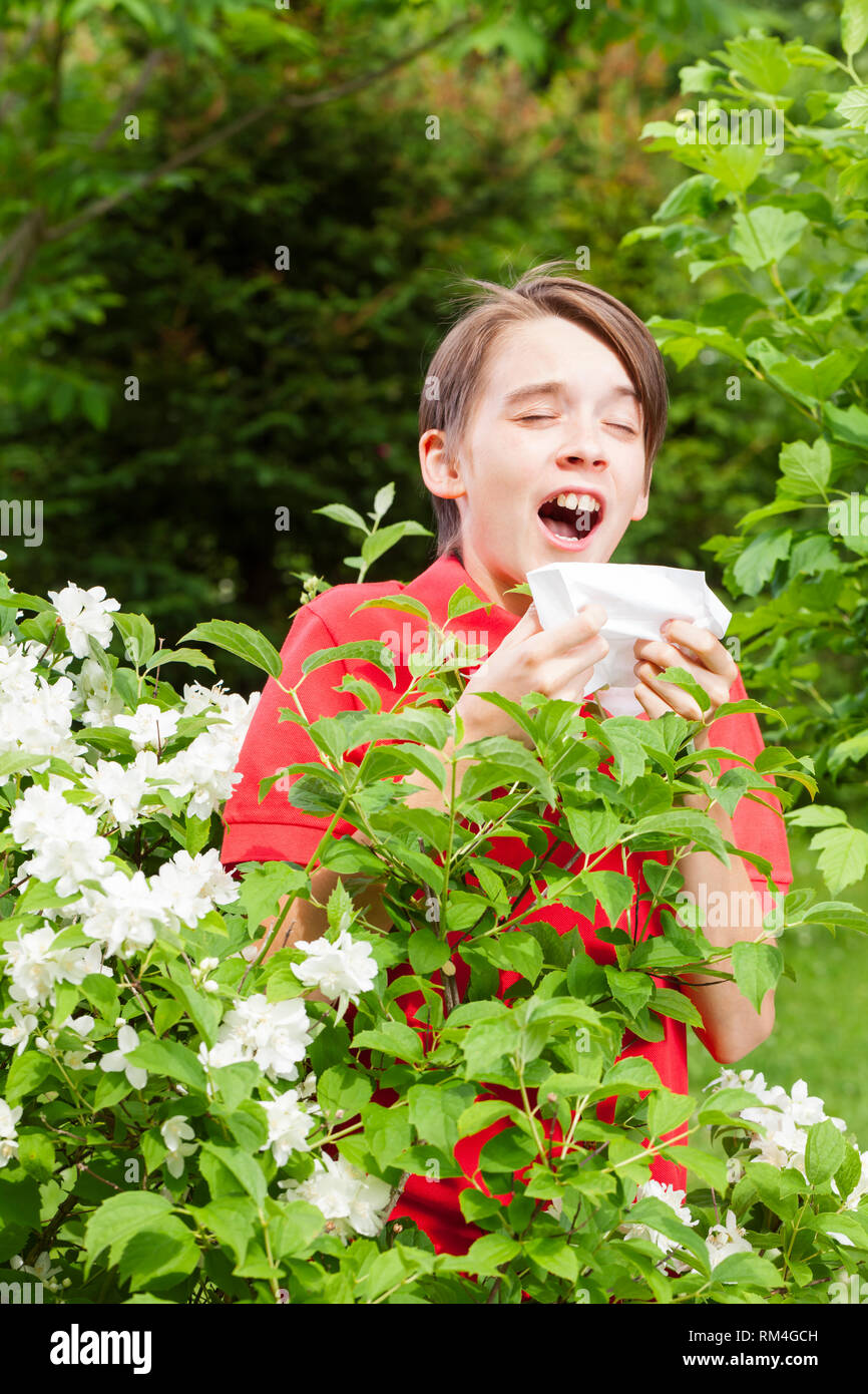 Teenager boy with seasonal influenza sneezing in a spring garden -  seasonal infection concept - Stock Image