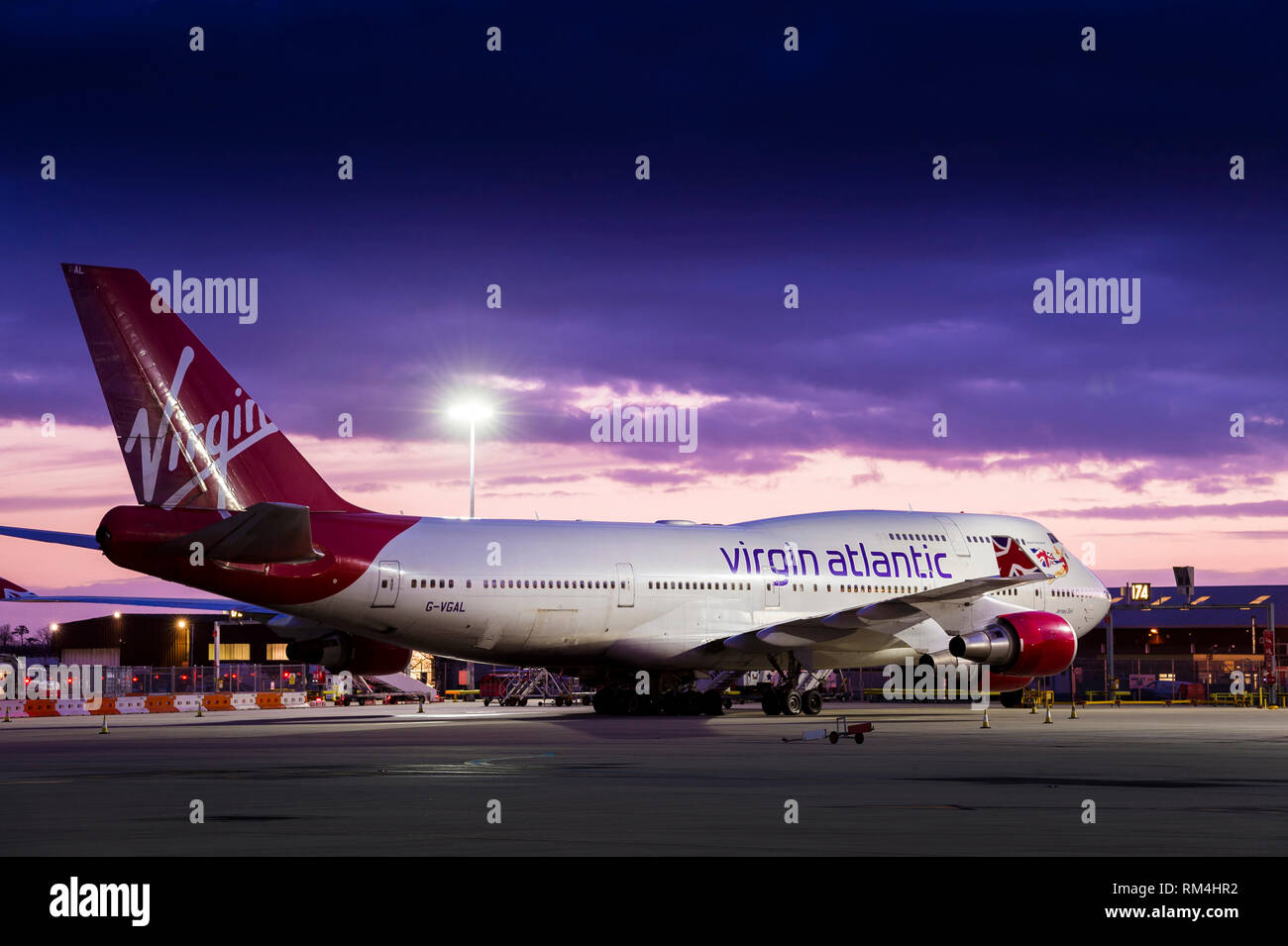 Virgin Atlantic aeroplane waiting on the apron at Gatwick airport at dusk. - Stock Image