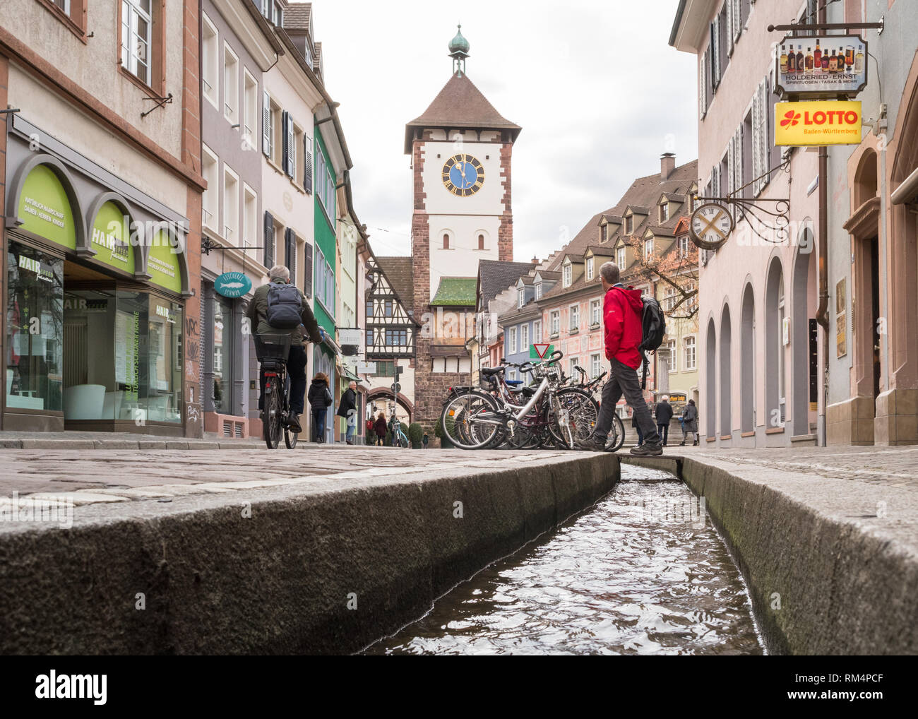 tourist crossing over a bachle - a water filled runnel - in front of the Schwabentor (Swabian city gate) in Freiburg im Breisgau, Germany, Europe - Stock Image