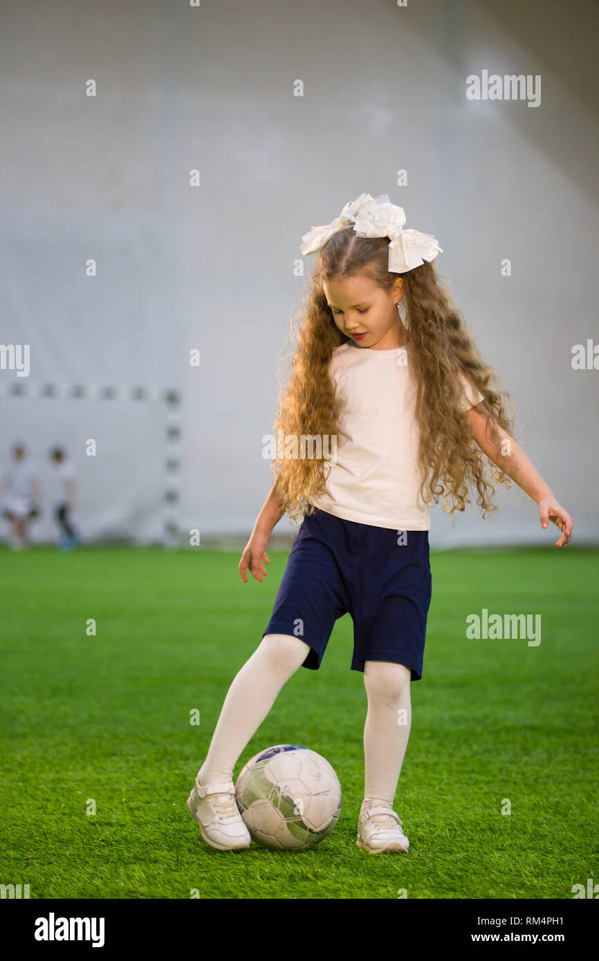 A little girl kicking the ball on the football field playing the game -  Stock Image