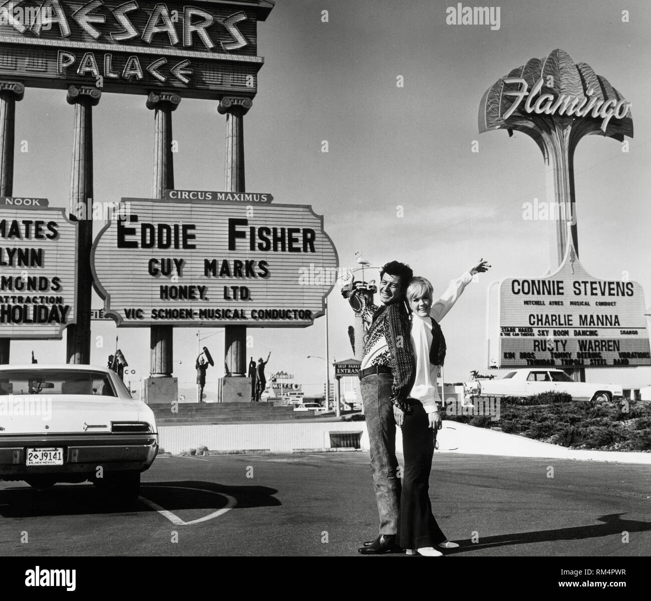Connie Stevens and her second husband, Eddie Fisher,  pointing to marquees displaying their names - Stevens at the Flamingo and Fisher at Caesar's Palace in Las Vegas, Nevada circa (1969)  File Reference # 33751_220THA - Stock Image