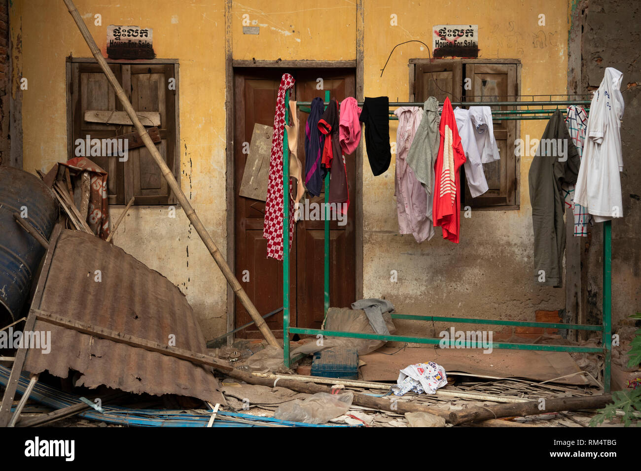 Cambodia, Kampot Province, Kampot city, Old Market area, investment opportunity, washing outside decaying old French colonial buildings - Stock Image