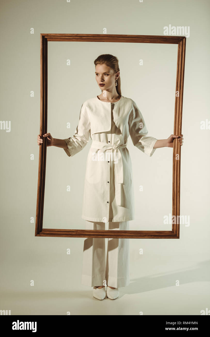 beautiful fashionable woman in white outfit posing with big wooden frame - Stock Image