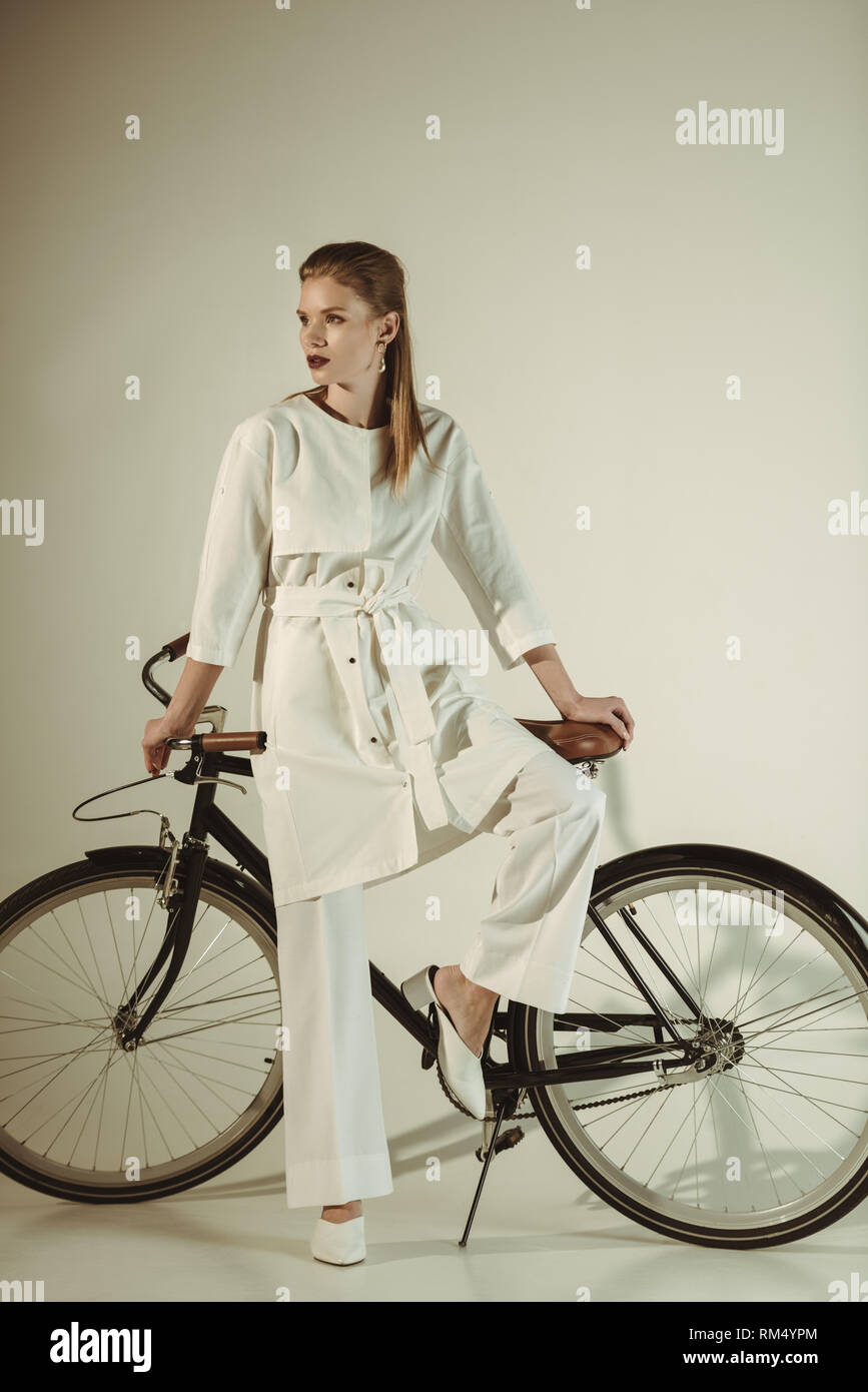 attractive stylish girl in white outfit posing on bicycle - Stock Image