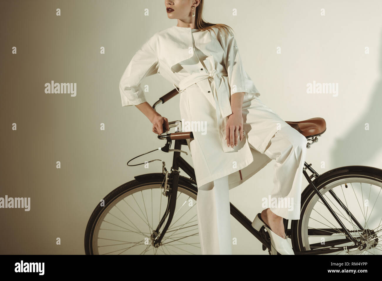 cropped view of stylish girl in white outfit posing on bicycle - Stock Image