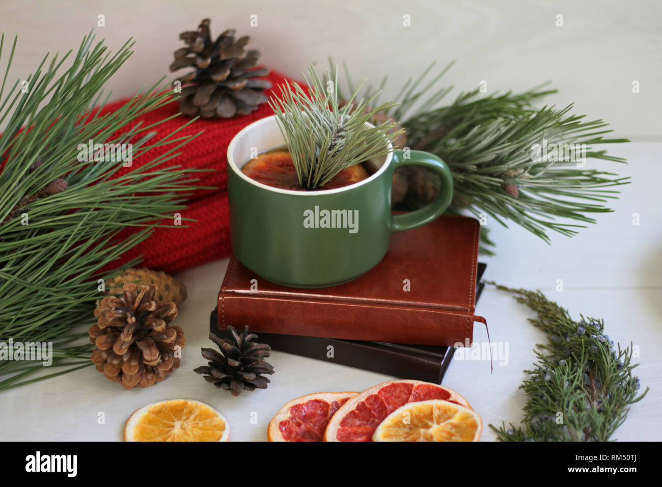 Warm composition on the table, a red scarf, dried oranges, heart-shaped cookies, a cup of hot tea with a slice of grapefruit and pine branches - Stock Image