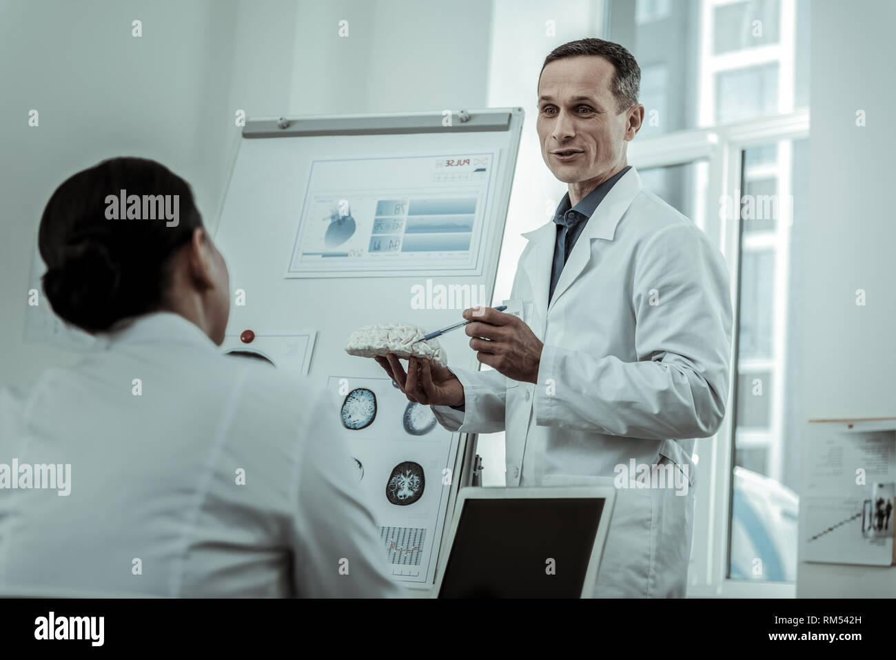 Couple of medical workers actively discussing brain disease - Stock Image