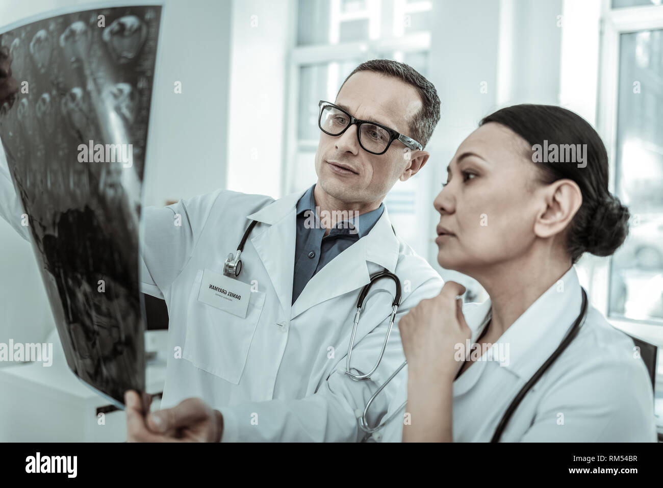 Executive doctors searching for fracture or crack in bones - Stock Image