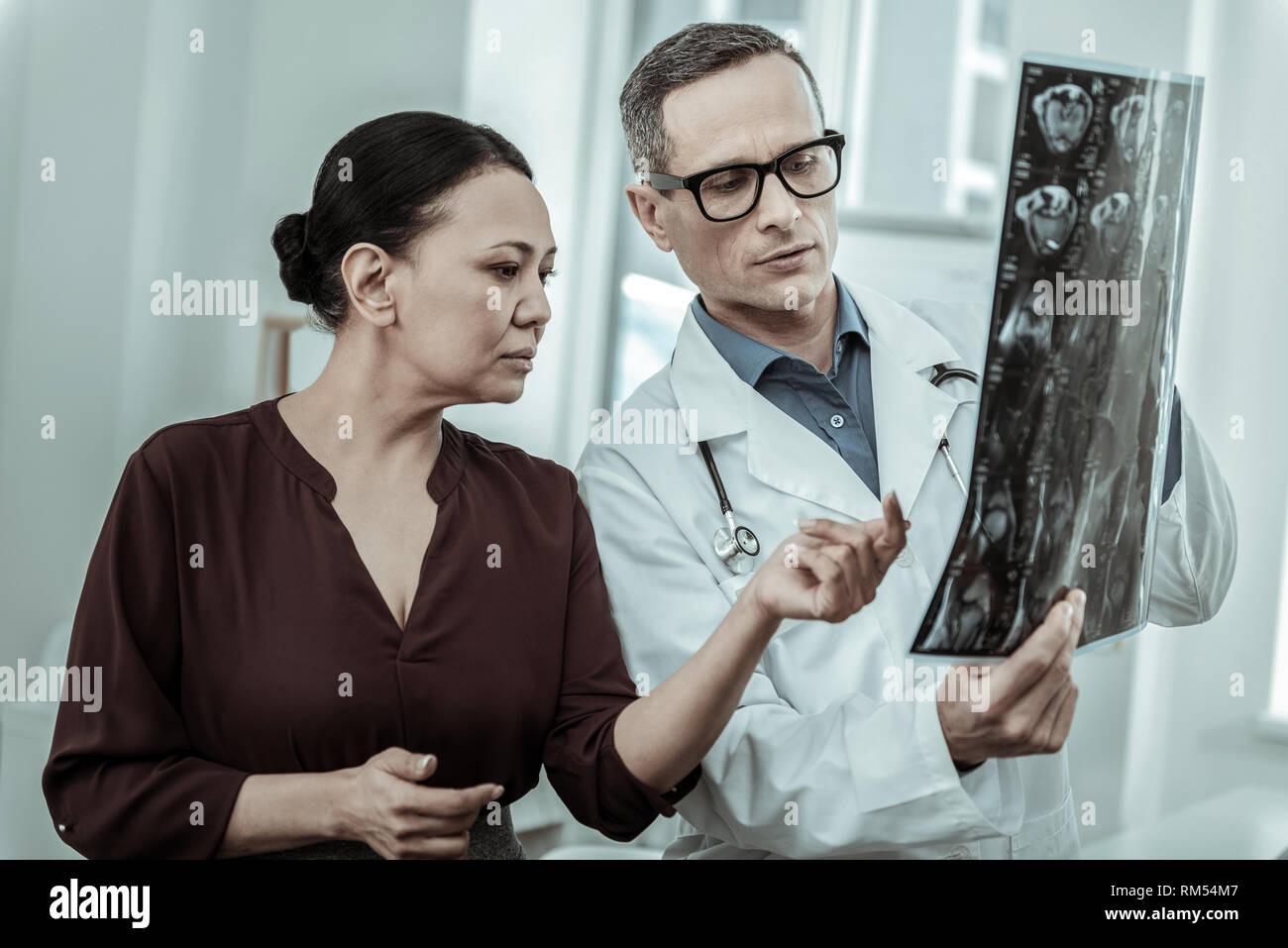 Attending doctor and his female patient staying nearby - Stock Image