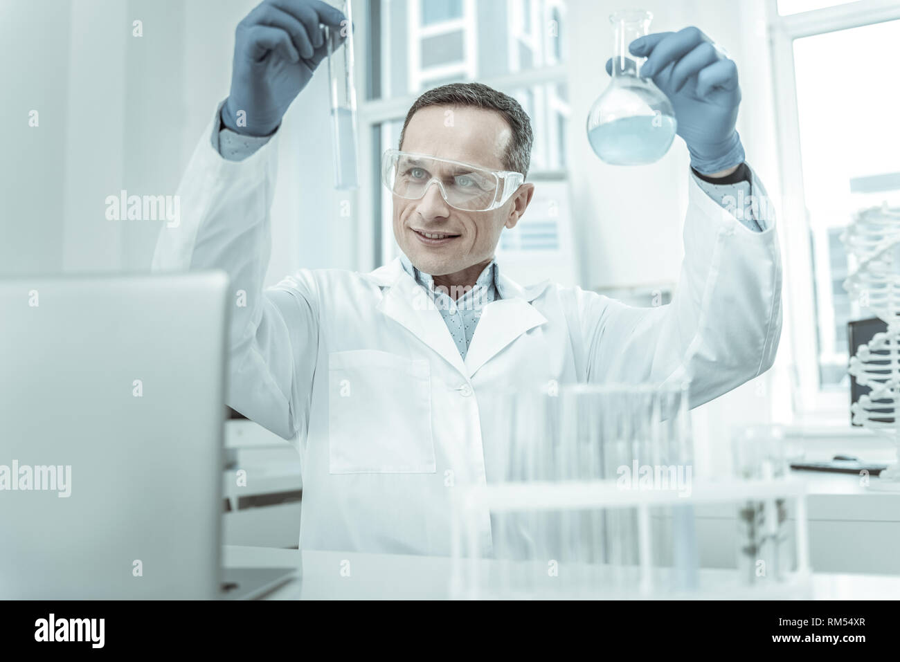 Contented scientist carrying tubes in both hands - Stock Image