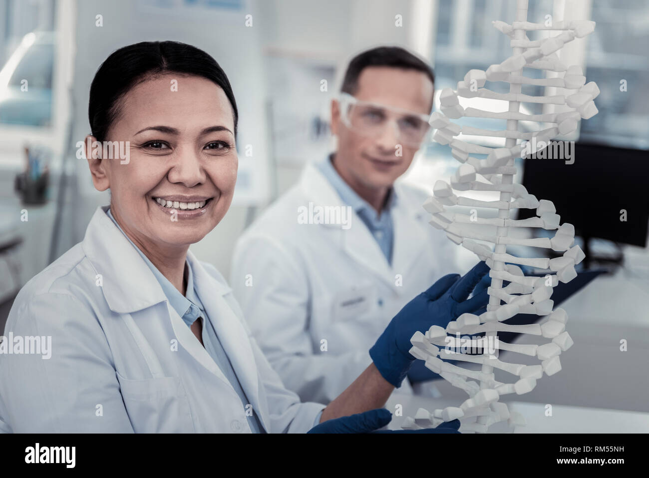 Smiling scientist trying to decode DNA secrets - Stock Image