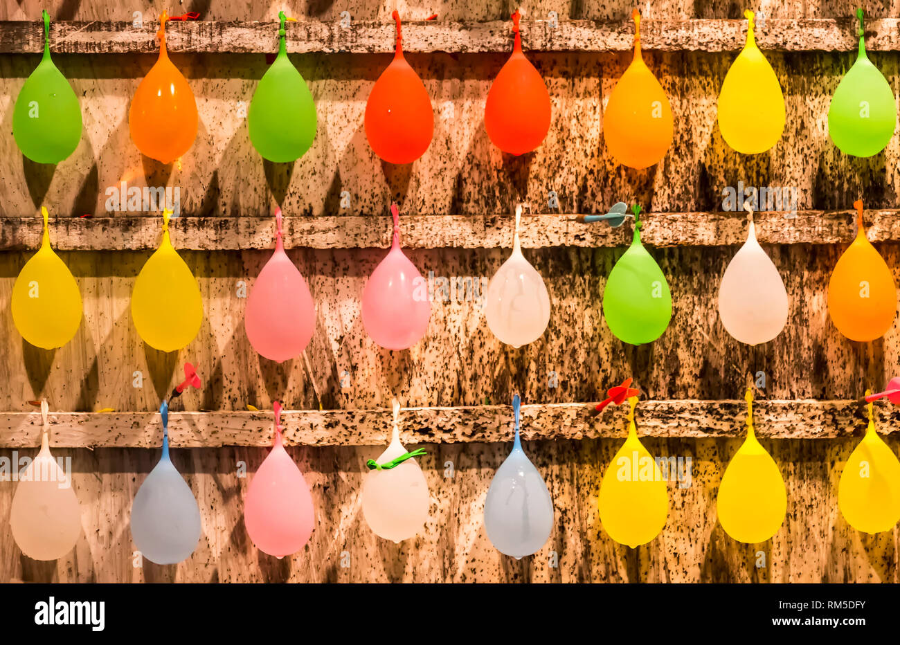 Multi-colored balloons against a wooden board at a amusement game stall along Kenting Street Night Market - Stock Image