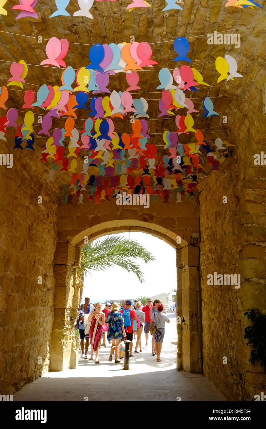 Day trippers and holidaymakers walking through the festooned archway leading into the main street on Tabarca Island, Alicante, Spain - Stock Image