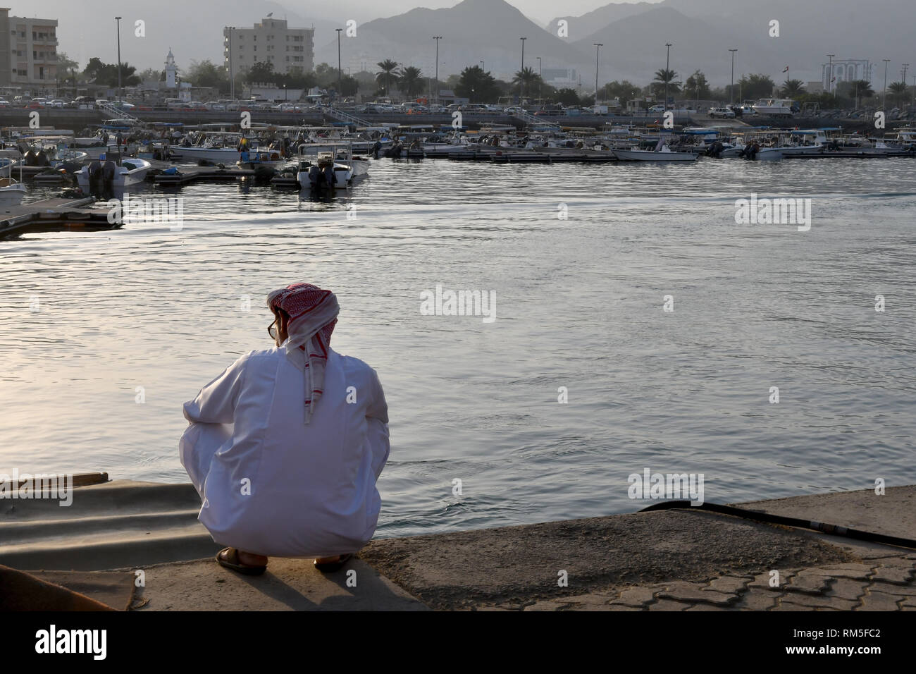 arabic man sitting on his haunches at the horbour of Khor Fakkan (Sharjah, UAE) - Stock Image
