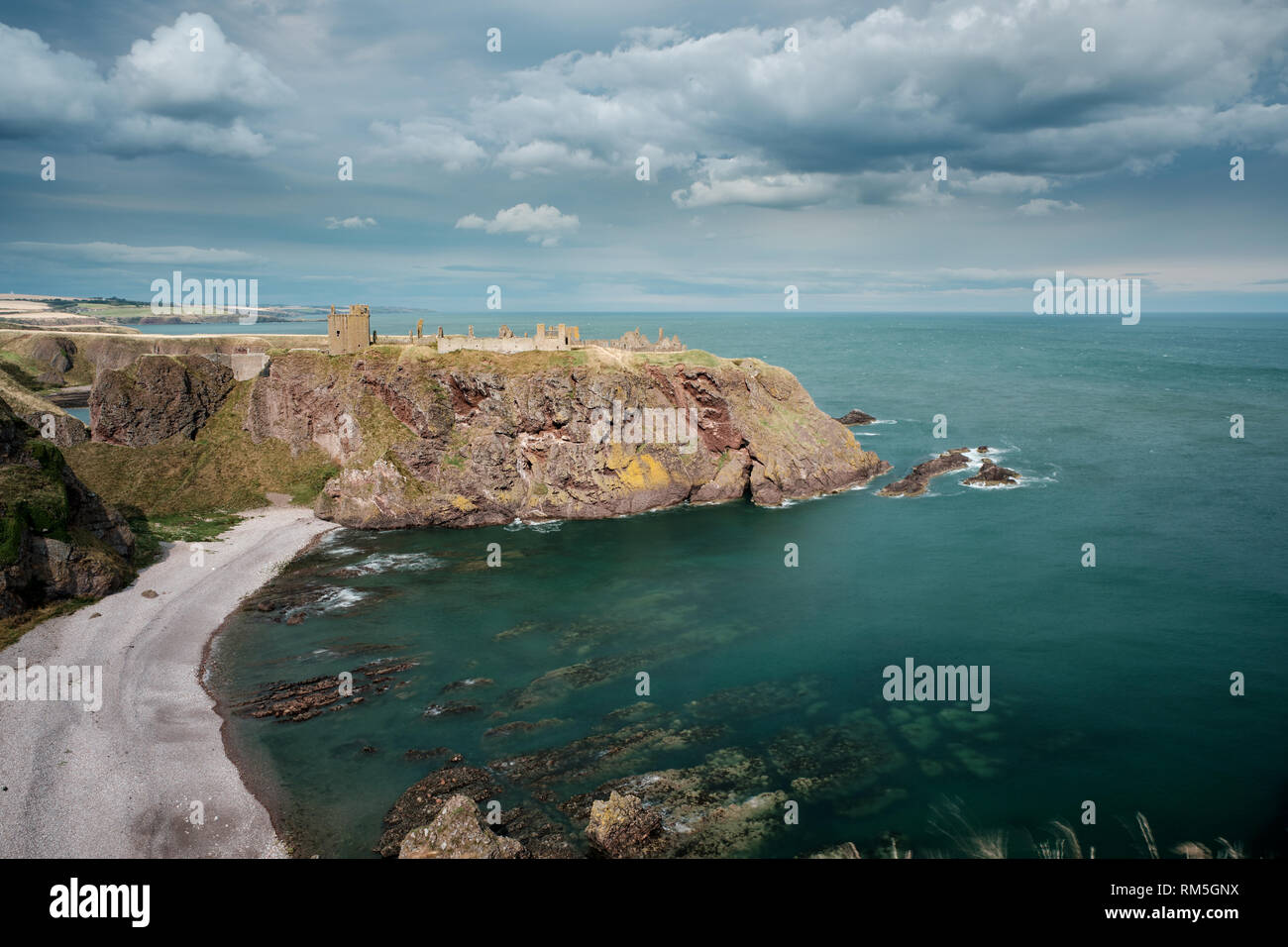 Dunnottar castle ruin and the surrounding coastline, bathed in sunshine with clouds overhead, Stonehaven, Aberdeenshire, Scotland - Stock Image