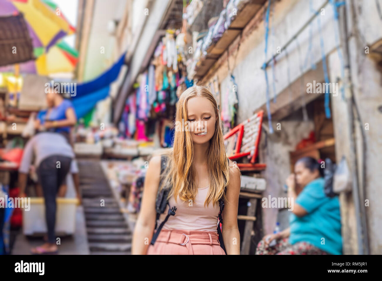 Woman traveler choose souvenirs in the market at Ubud in Bali, Indonesia - Stock Image