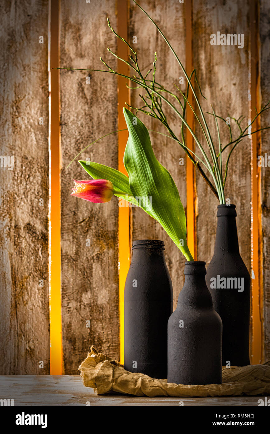 Flower red Tulip an wooden Table in a black vase Stock Photo