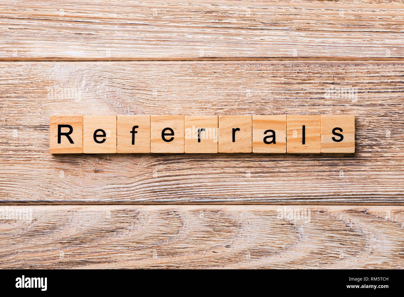 REFERRALS word written on wood block. REFERRALS text on wooden table for your desing, concept. - Stock Image