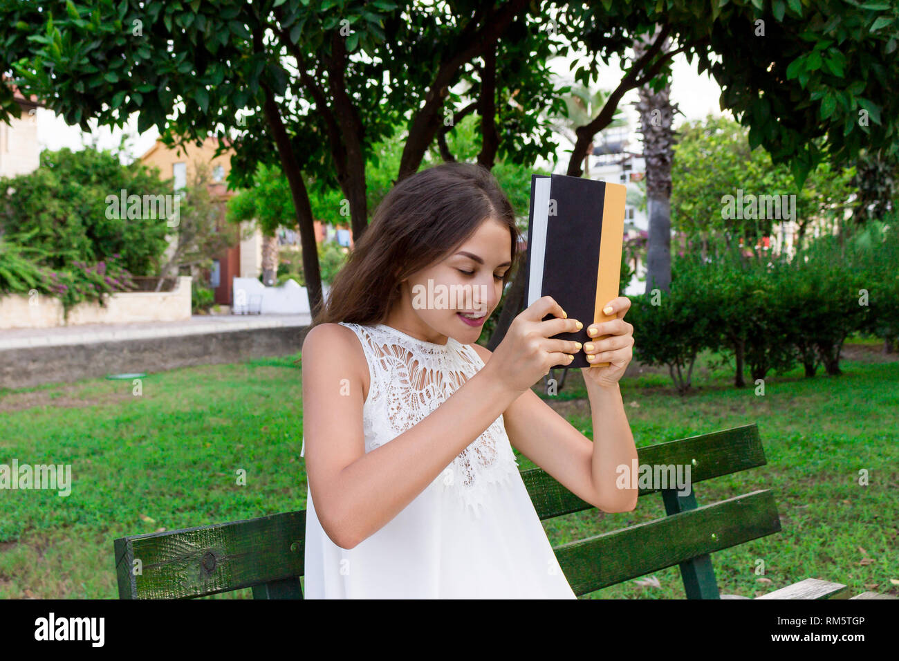 Pretty girl is very angry and is hitting the book with the head sitting on the bench outside. - Stock Image