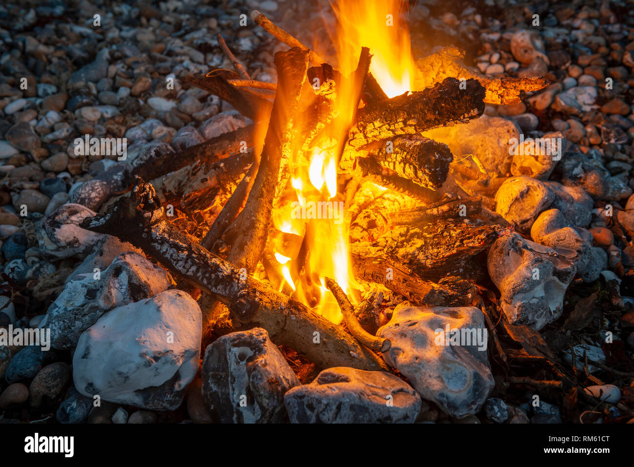 Small fire on a pebble beach - Stock Image