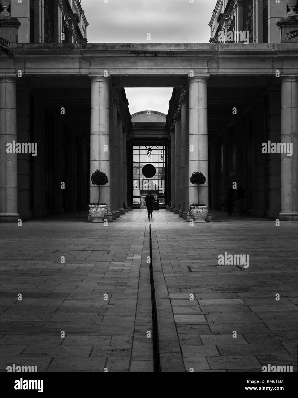 A man walks through an ostentatious tunnel surrounded by awesome architecture in black and white - Stock Image