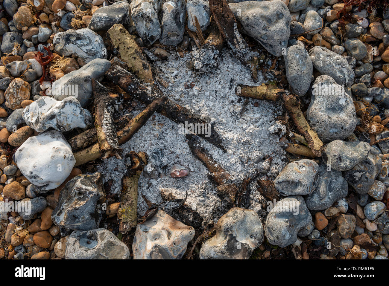 Remains of a small fire on a pebble beach - Stock Image