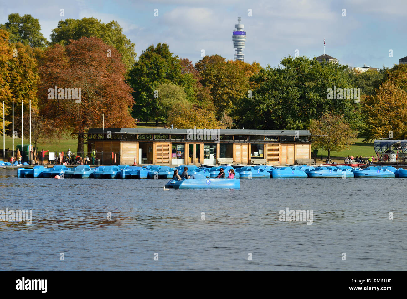 Blue leisure boats or Pedalos on the Serpentine lake, Hyde Park, London, United Kingdom - Stock Image