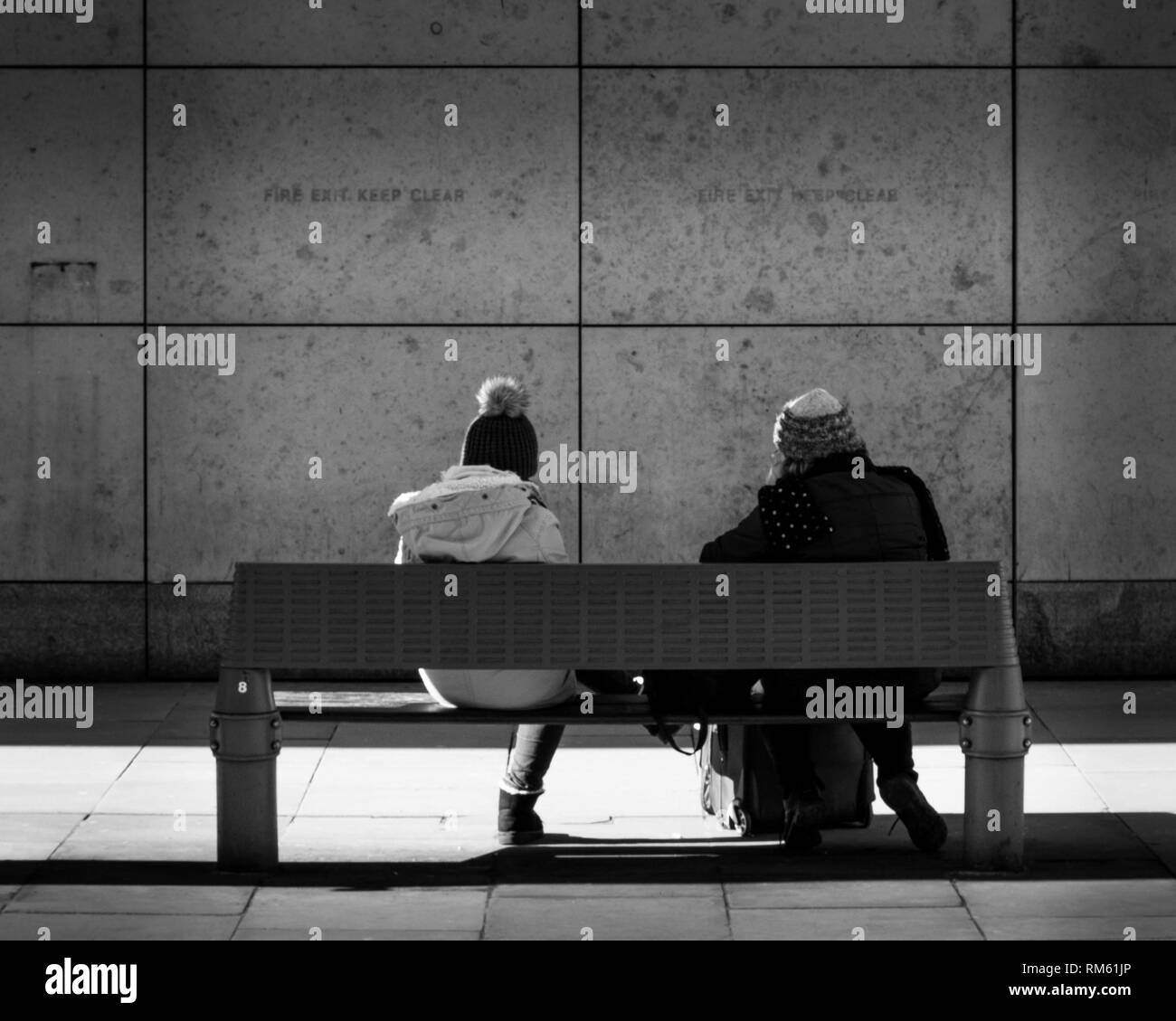 Two Women With Their Backs To Camera Sit On A Bench In Manchester Wearing Winter Clothing And Facing A Walll Stock Photo Alamy