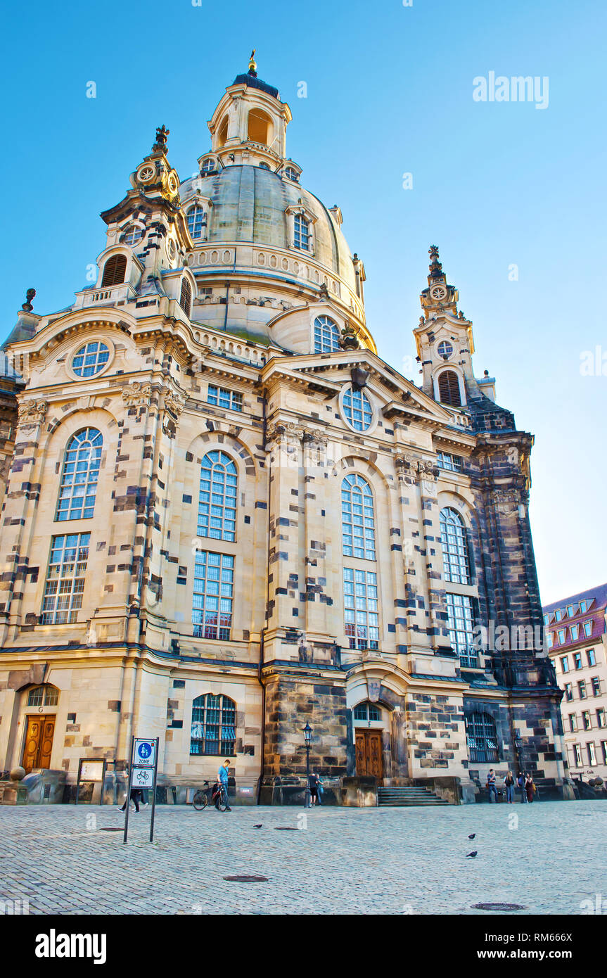 A square in front of Frauenkirche Dresden, Germany. Amazing architecture with high dome and many arch windows. Cloudless spring day. View of the ancie - Stock Image