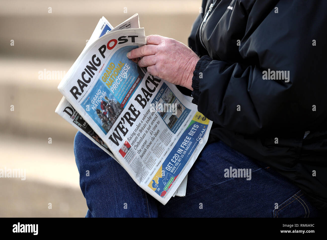 A racegoer reads the Racing Post featuring the front page headline 'We're Back' during the Injured Jockeys Fund Charity Raceday at Plumpton Racecourse. - Stock Image