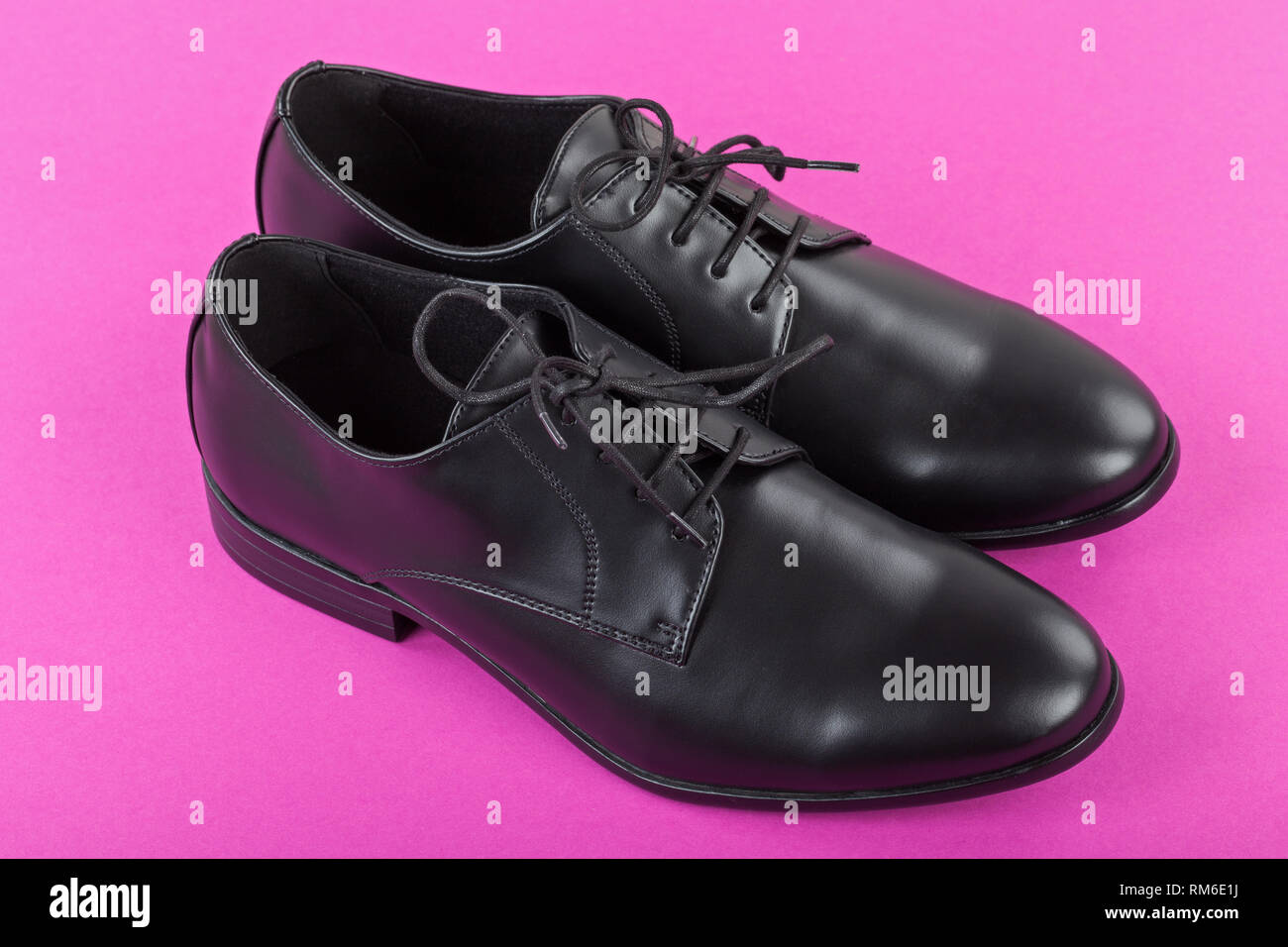 Close up picture of mens footwear Black leather elegant shoes on pink background Stock Photo
