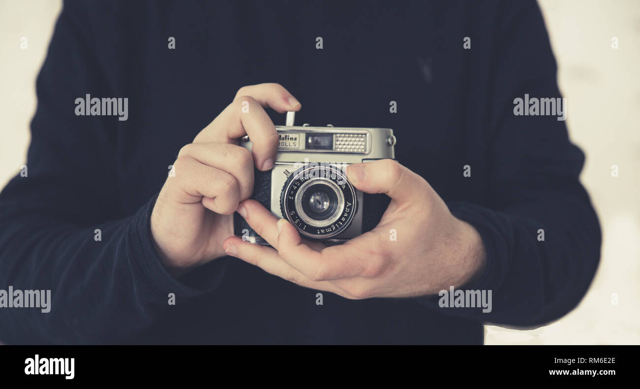 A midsection of a male photographer focussing the lens whilst holding a retro or old fashioned 35mm camera in a hobby lifestyle image - Stock Image