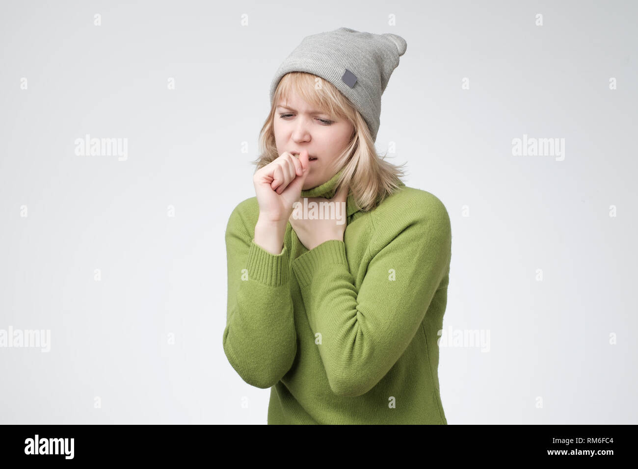 Unhealthy young blonde woman coughing a lot, suffering with cough, has a chest pain - Stock Image