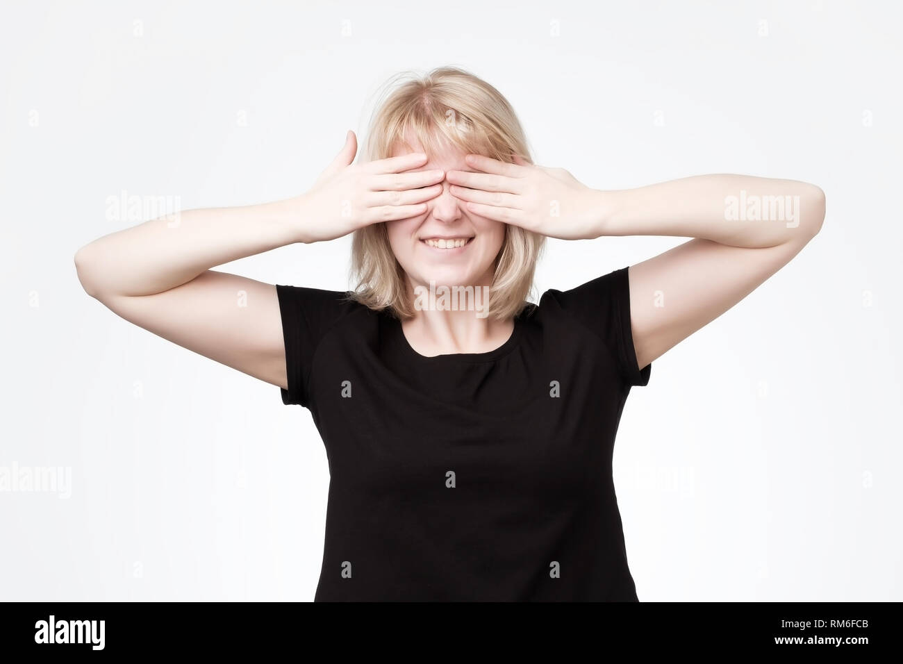 Woman covering eyes with hands and smiling broadly, being intrigued while waiting for surprise - Stock Image