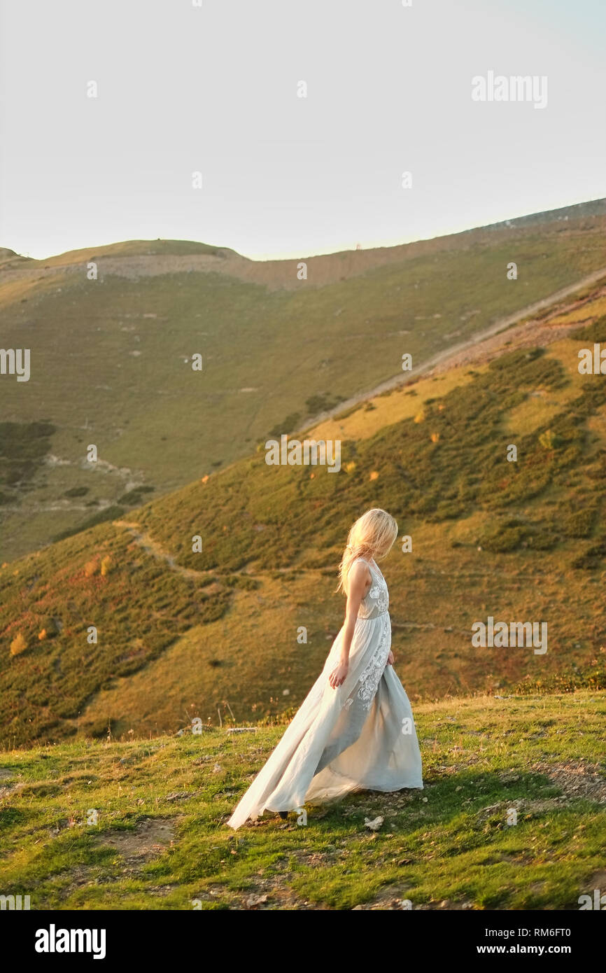 Bride in vintage wedding dress running away at sunset. Spectacular mountain landscape in the background. Travelers love to party. runaway Bride Stock Photo