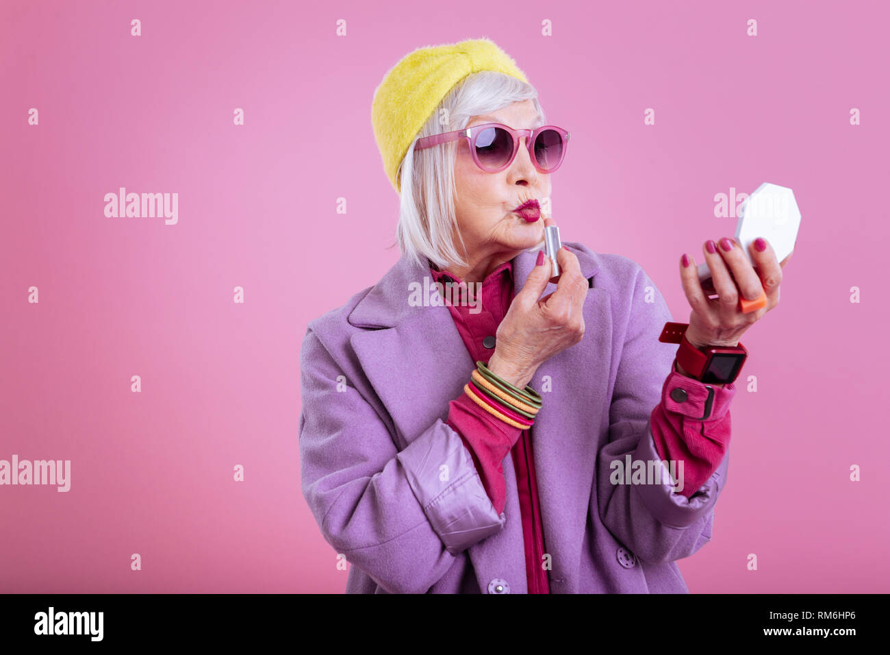 Cute lovely retired woman making funny face coloring lips Stock Photo