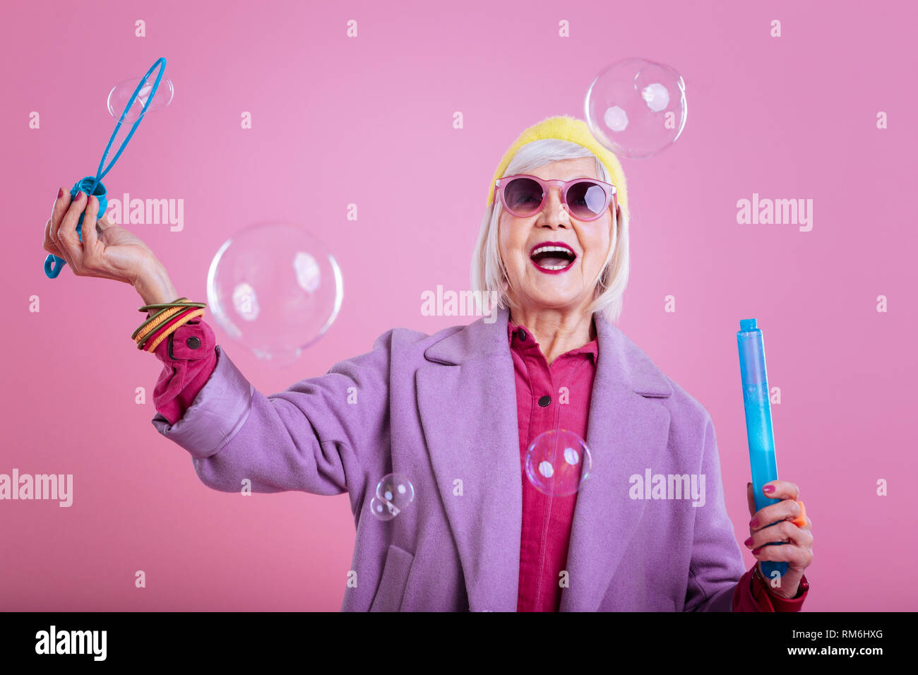 Retired lady feeling excited while watching soap bubbles - Stock Image