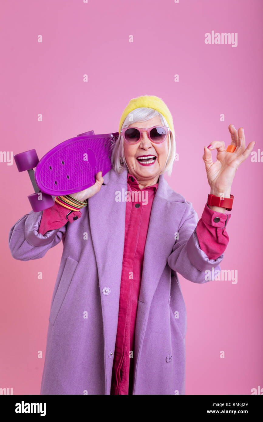 Elderly lady feeling truly satisfied after riding skateboard - Stock Image