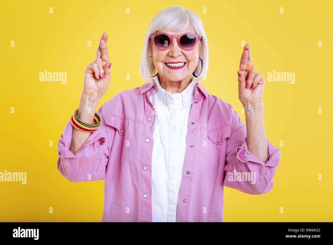 Funny elderly lady in sunglasses keeping her fingers crossed - Stock Image
