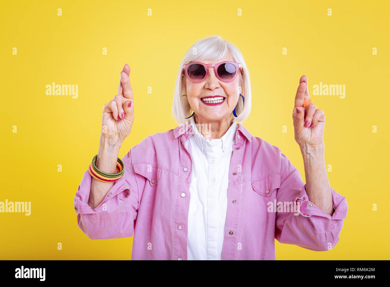 Stylish modern retired woman with bright manicure having fingers crossed - Stock Image