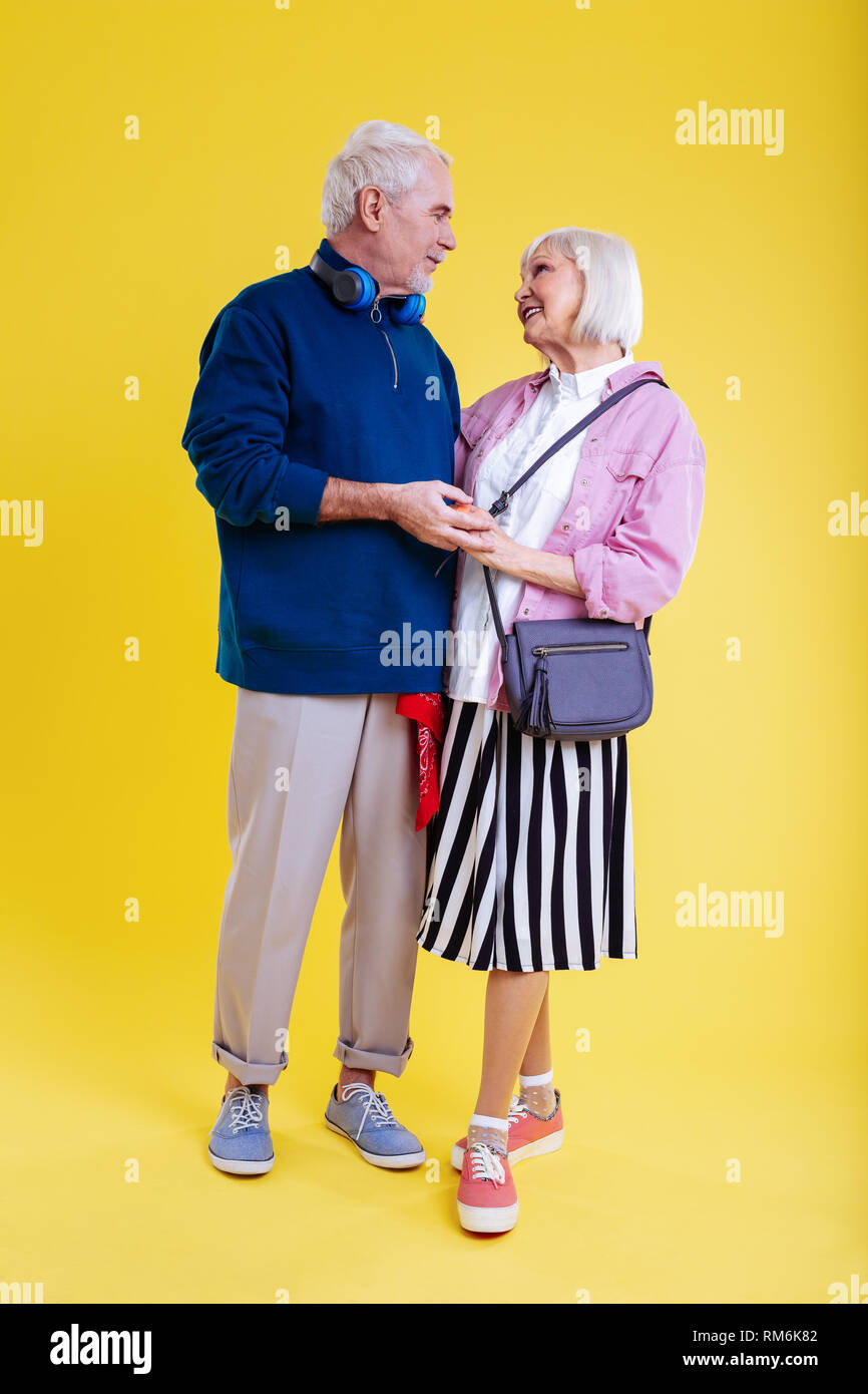 Modern retired couple wearing sneakers looking at each other - Stock Image