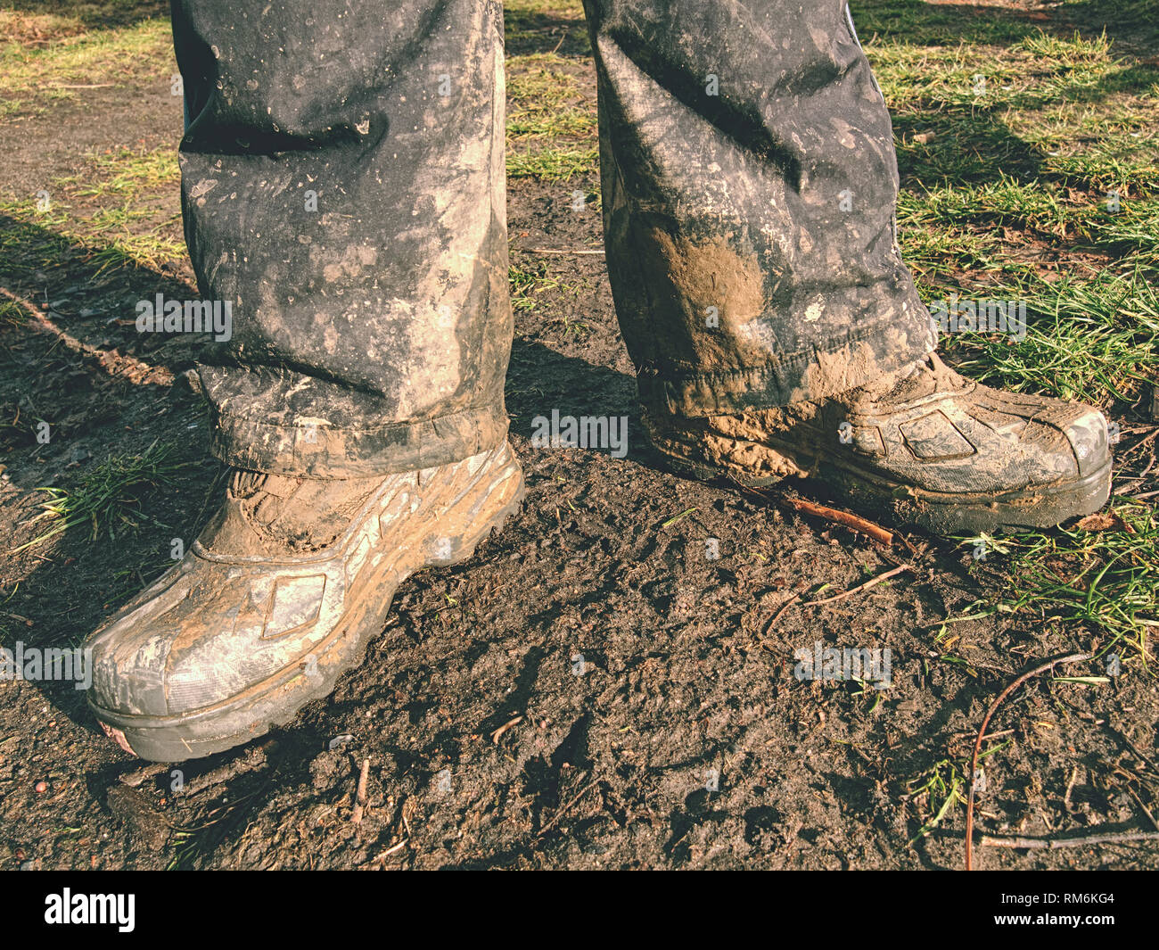 Farmer wearing muddy boots in daily business. Muddy rubber boot in horse farm area Stock Photo