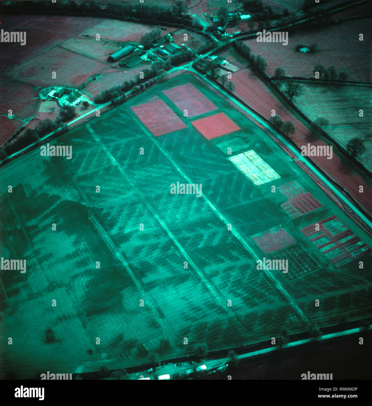 False colour infrared aerial image of a mainly fallow field dark moisture content showing its drainage pattern with pink red patches of vegetation - Stock Image