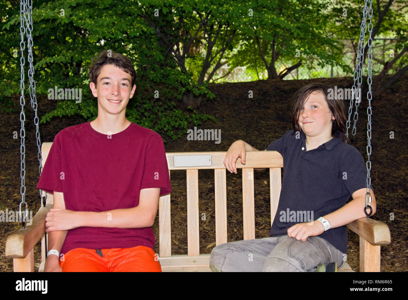 2 teen boys; wood seat swing; friends; woods; smiling; happy; relaxing, wrist bands, horizontal; MR - Stock Image