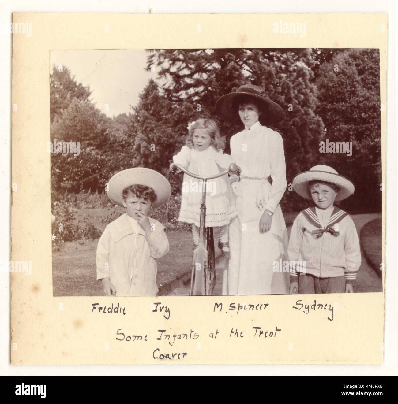 Edwardian photograph of an attractive mother in a white summer blouse and skirt walking with her children in the park or a garden. The youngest child is  balanced on the mother's bicycle,the boys wear fashionable sailor suits and straw hats, circa 1910, U.K. - Stock Image